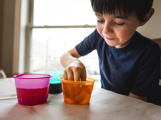Boy making Easter eggs on table while sitting against window at home - CAVF52772