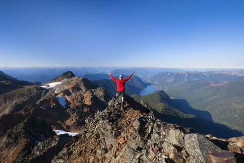 Rear view of hiker with arms raised standing on mountain against clear sky - CAVF52796