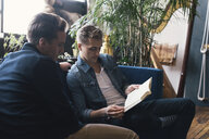 Gay men looking at book while sitting on sofa at home - CAVF52811
