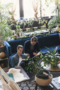 Homosexual couple reading books while sitting amidst potted plants at home - CAVF52817