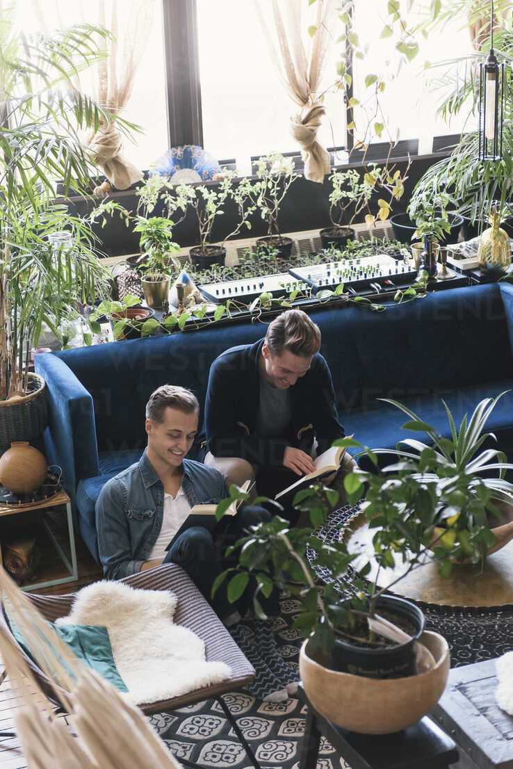 Homosexual couple reading books while sitting amidst potted plants at home - CAVF52817 - Cavan Images/Westend61