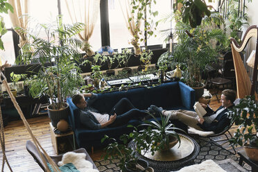 High angle view of gay couple relaxing amidst potted plants at home - CAVF52820