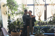 Gay couple romancing while standing against potted plants at home - CAVF52823