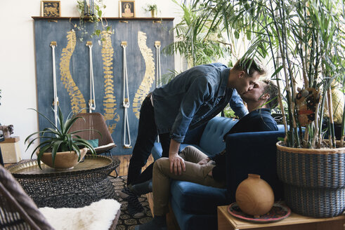 Homosexual gay couple kissing by potted plants at home - CAVF52826
