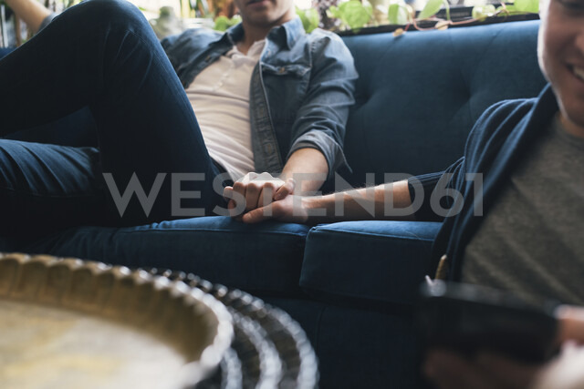 Midsection of gay man holding boyfriend's hand while relaxing on sofa at home - CAVF52829