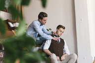 Gay man adjusting boyfriend's necktie against wall at home - CAVF52835