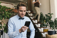 Gay man using smart phone while boyfriend walking down steps in background at home - CAVF52850
