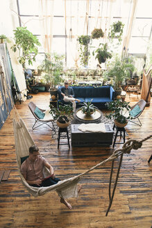 High angle view of gay man relaxing in hammock while boyfriend sitting on sofa at loft apartment - CAVF52856