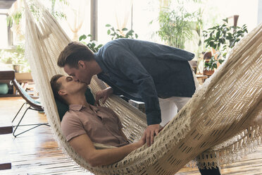 Gay man kissing boyfriend lying in hammock at home - CAVF52859