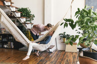 Gay man looking at boyfriend lying in hammock - CAVF52862