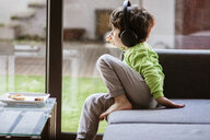 Thoughtful of boy listening music while eating food on sofa by window at home - CAVF52877