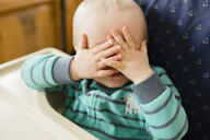 Playful baby boy covering eyes while playing peekaboo on high chair at home - CAVF52897