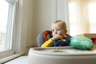 Cute thoughtful baby boy with plastic bowl and spoon sitting on high chair at home - CAVF52900