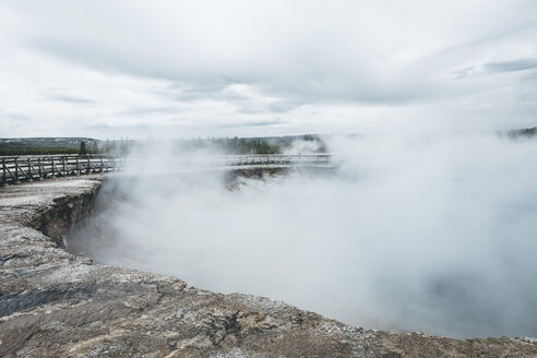 Smoke emitting from hot spring against cloudy sky at Yellowstone National Park - CAVF52906