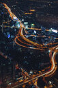 Aerial view of light trails on road amidst city at night - CAVF52924