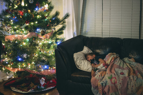 Boy sleeping on sofa by illuminated Christmas tree at night - CAVF52951