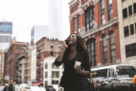 Happy businesswoman with coffee talking on smart phone while standing on sidewalk in city - CAVF52969
