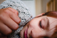 Close-up of smiling girl sleeping on bed at home - CAVF52996