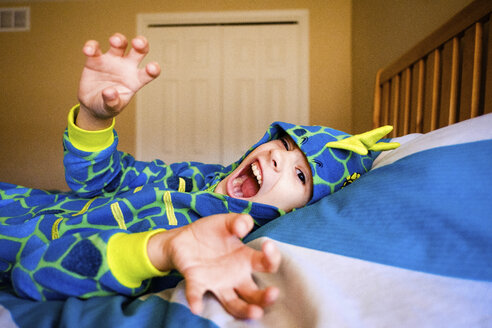 Portrait of girl wearing costume screaming while lying on bed at home during Halloween - CAVF52999