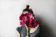 Woman holding pink flowers while standing by white wall at home - CAVF53097