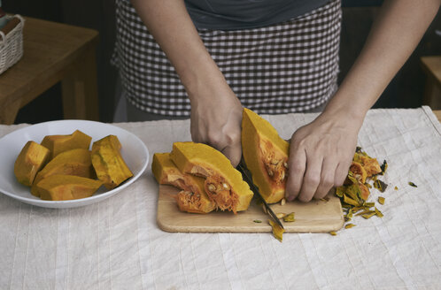 Midsection of woman cutting pumpkin on table at home - CAVF53118