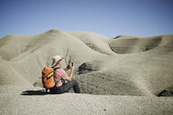 Backpacker photographing through mobile phone while sitting on sand at desert against clear sky - CAVF53142