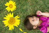 High angle view of cute happy girl lying by sunflowers on grassy field - CAVF53151