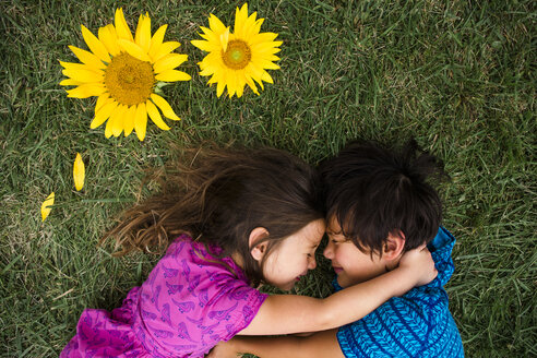 High angle view of siblings embracing while lying on grassy field - CAVF53154