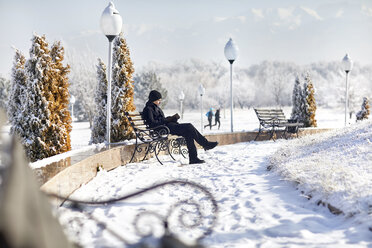 Full length of young man wearing black warm clothing while reading book on park bench during winter - CAVF53163