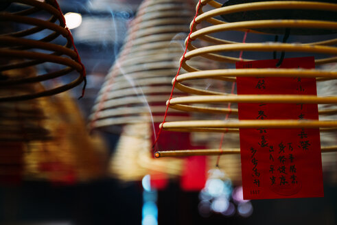 China, Hong Kong, Ma Mo Temple, burning incense spiral with prayer on red paper, close-up - GEM02451