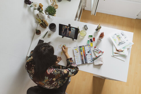 Illustrator painting at work desk in an atelier using digital tablet, top view - AFVF01925