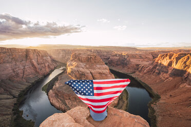 USA, Arizona, Colorado River, Horseshoe Bend, young man on viewpoint with American flag - KKAF02845