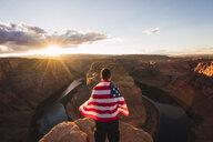 USA, Arizona, Colorado River, Horseshoe Bend, young man on viewpoint with American flag - KKAF02848
