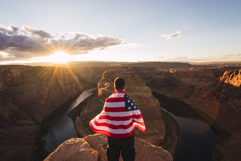 USA, Arizona, Colorado River, Horseshoe Bend, young man on viewpoint with American flag - KKAF02848