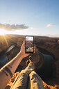 USA, Arizona, Colorado River, Horseshoe Bend, young man on viewpoint, holding smartphone - KKAF02851