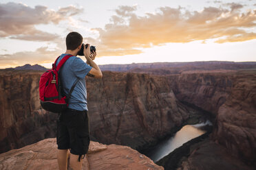 USA, Arizona, Colorado River, Horseshoe Bend, young man on viewpoint, photographing - KKAF02854