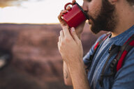 Young man drinking, red cup - KKAF02857