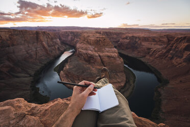 USA, Arizona, Colorado River, Horseshoe Bend, young man on viewpoint, notebook - KKAF02860