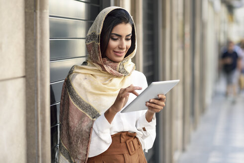 Spain, Granada, young muslim woman wearing hijab using tablet outdoor - JSMF00554