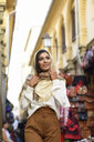 Spain, Granada, young muslim tourist woman wearing hijab during sightseeing in the city - JSMF00560