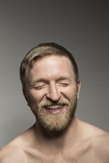 Portrait of laughing bearded man with eyes closed - VGF00090