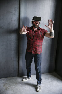 Excited bearded man wearing VR glasses - REAF00463
