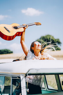 Happy young woman holding her guitar aloft, standing in her van on a road trip - OCMF00081