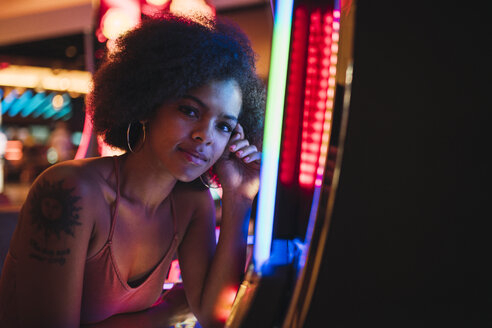USA, Nevada, Las Vegas, portrait of young woman at slot machine in a casino - KKAF02888