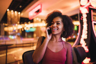 USA, Nevada, Las Vegas, portrait of happy young woman on cell phone in a casino - KKAF02891