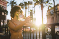 USA, Nevada, Las Vegas, happy young woman taking a selfie in the city - KKAF02897