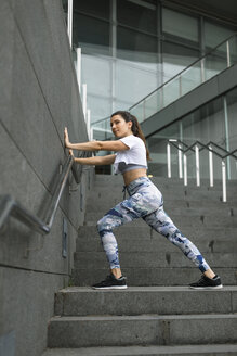 Young woman doing stretching exercise on stairs - FMGF00077