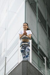 Fit young woman in the city holding cell phone - FMGF00080