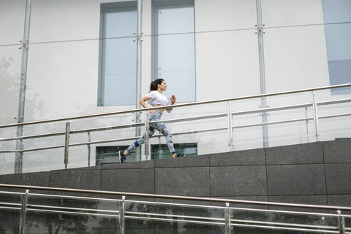 Young woman running along building in the city - FMGF00083