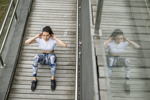 Young woman doing situps on a footbridge - FMGF00086